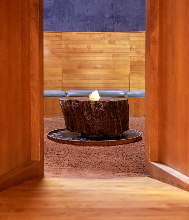 spa room surrounded by wooden bench seating with a large crystal table in the centre