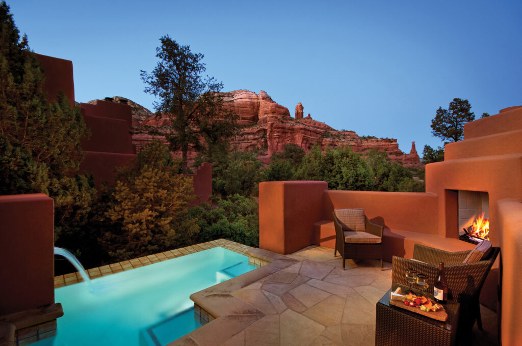 spa pool next to a red concrete outdoor fireplace during dusk