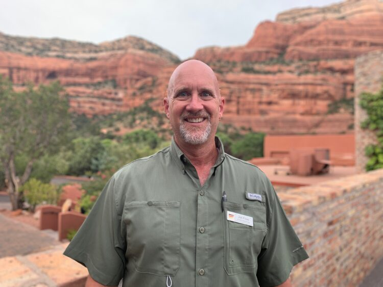 Jim Foss smiling in front of a large red rock formation