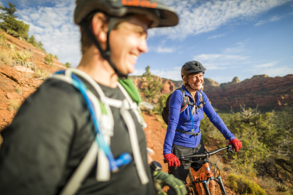 man and woman smiling while on a bike ride through a large red rock formation