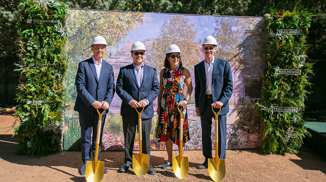 4 people smiling in front of a backdrop wearing hard hats and holding shovels