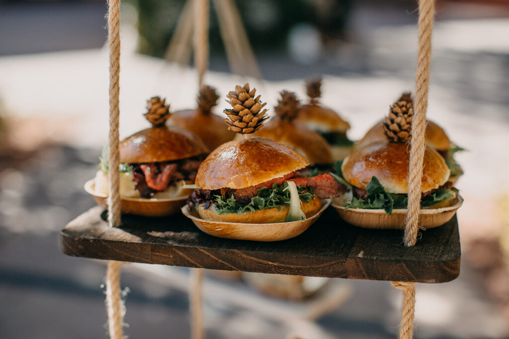 sandwiches on wooden plates topped with decorative pine cones