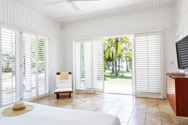 white room with shutter doors with view of palm trees