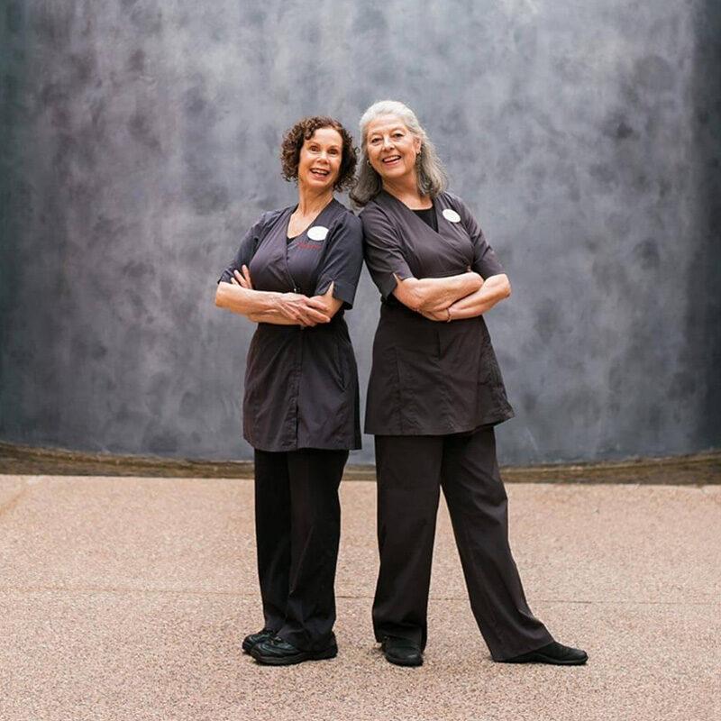 2 women in uniforms standing near gray wall