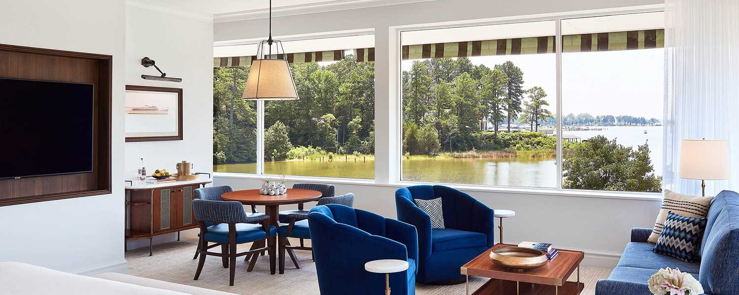 hotel suite seating area next to windows opening to lake view