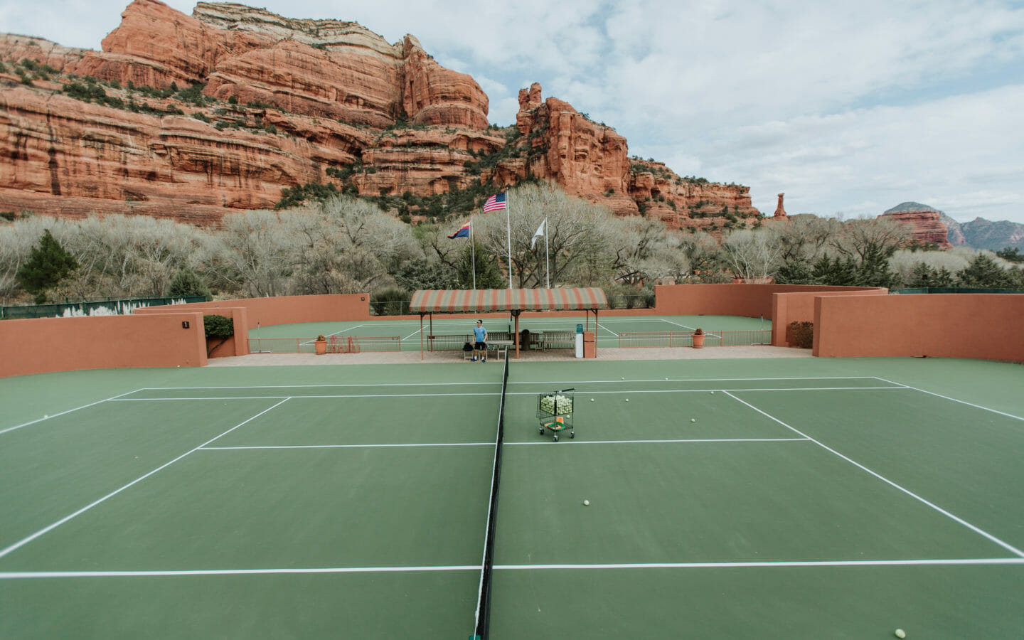 tennis courts below a rock formation surrounded by trees