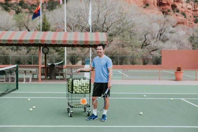 person standing on a tennis court beside the basket of tennis balls