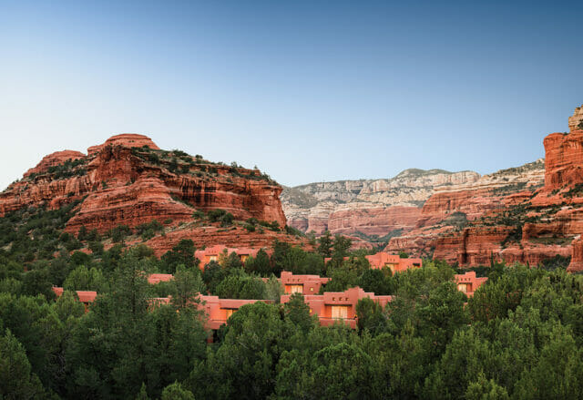clay resort buildings in a rock canyon surrounded by trees during daytime