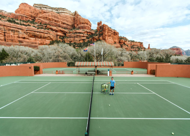 man standing on tennis court viewing Sedona in Arizona under white and blue sky during daytime