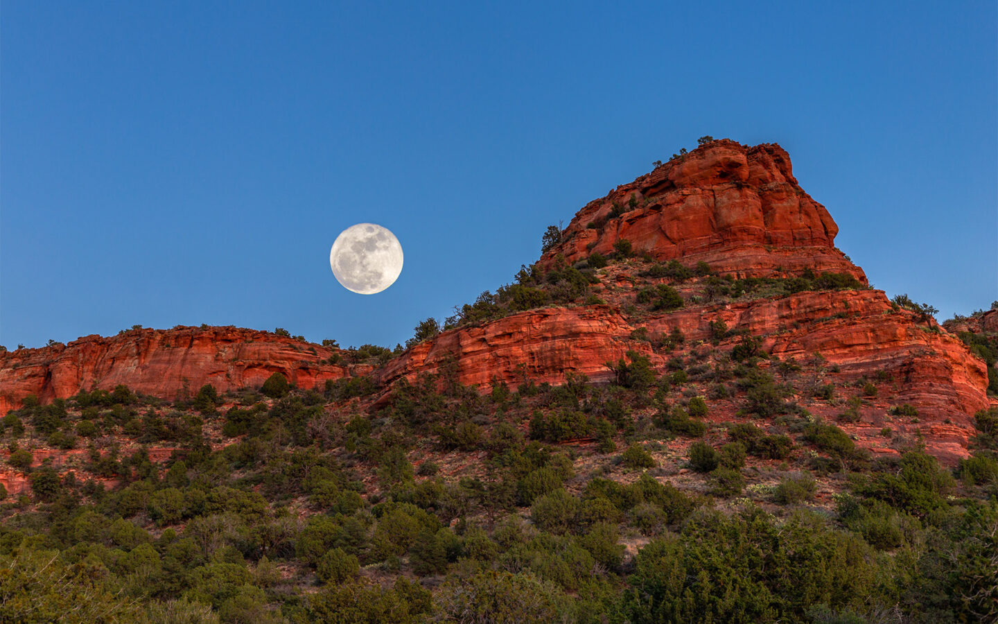 full moon rising over Sedona red rocks