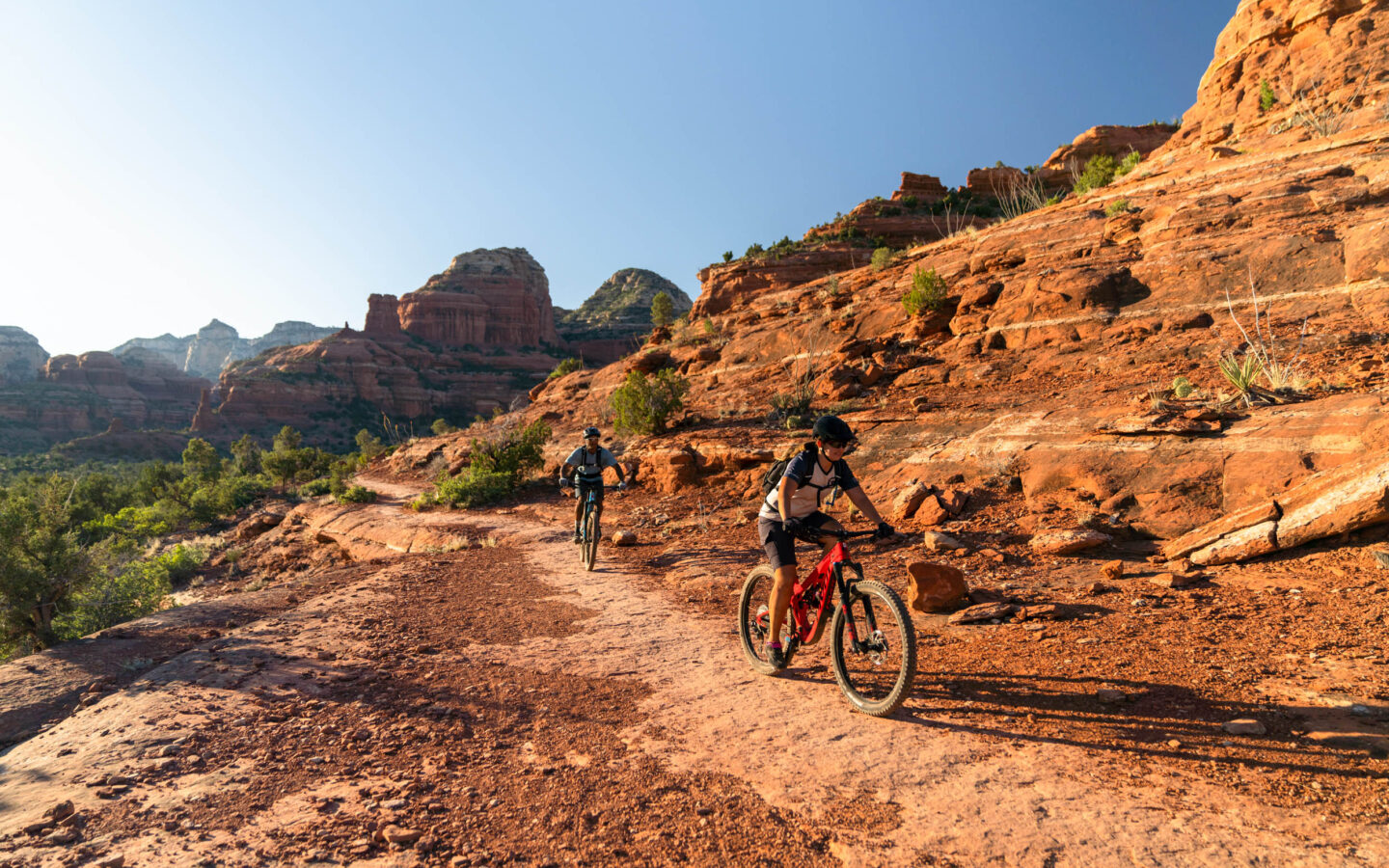 Two people mountain biking through red stone canyon