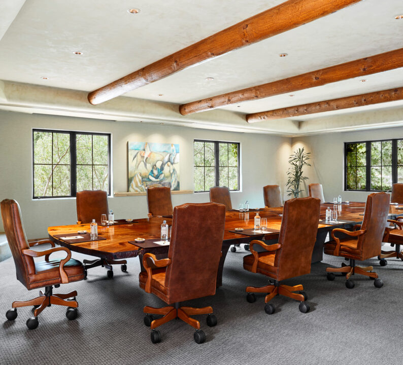 Boardroom with large wooden table and leather chairs