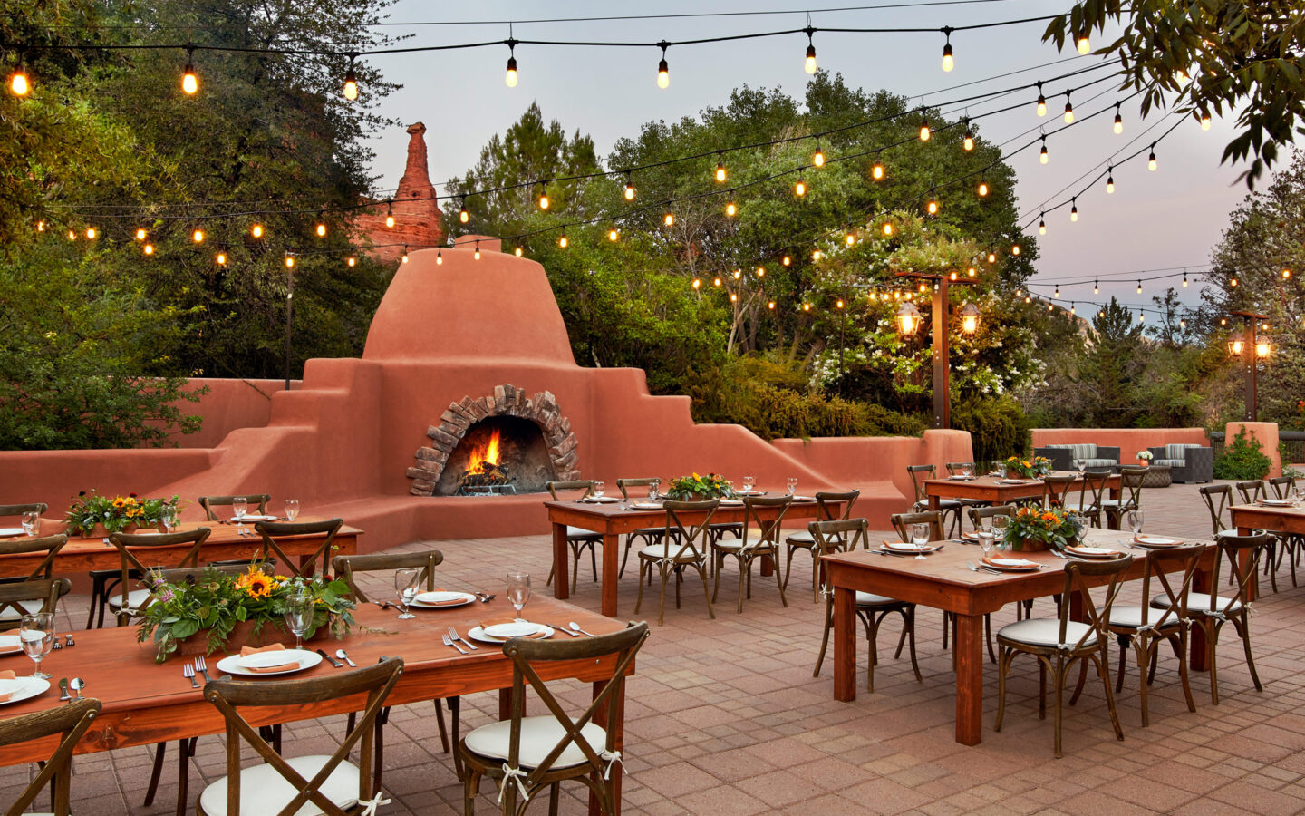 Dining tables outside near a large red stone fireplace
