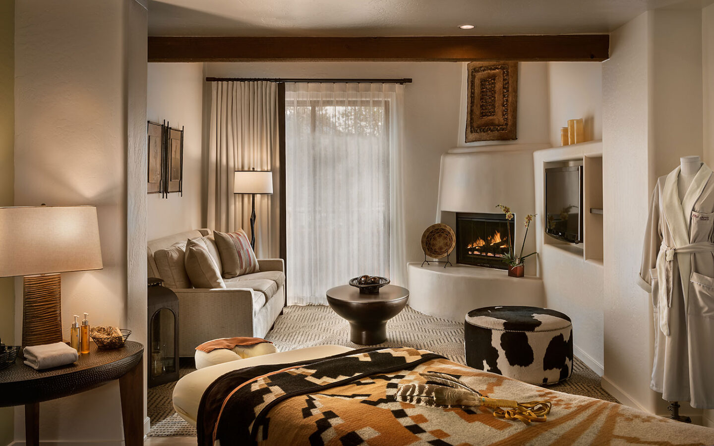 spa room with spa bed, sofa, fireplace and bath robe
