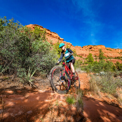 Mountain biker with red canyon and blue sky in the background