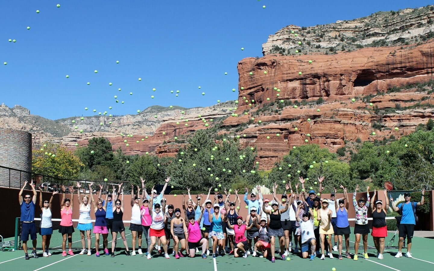 group of people on tennis court throwing tennis balls in the air
