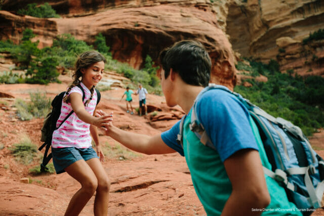 man assisting young girl while hiking