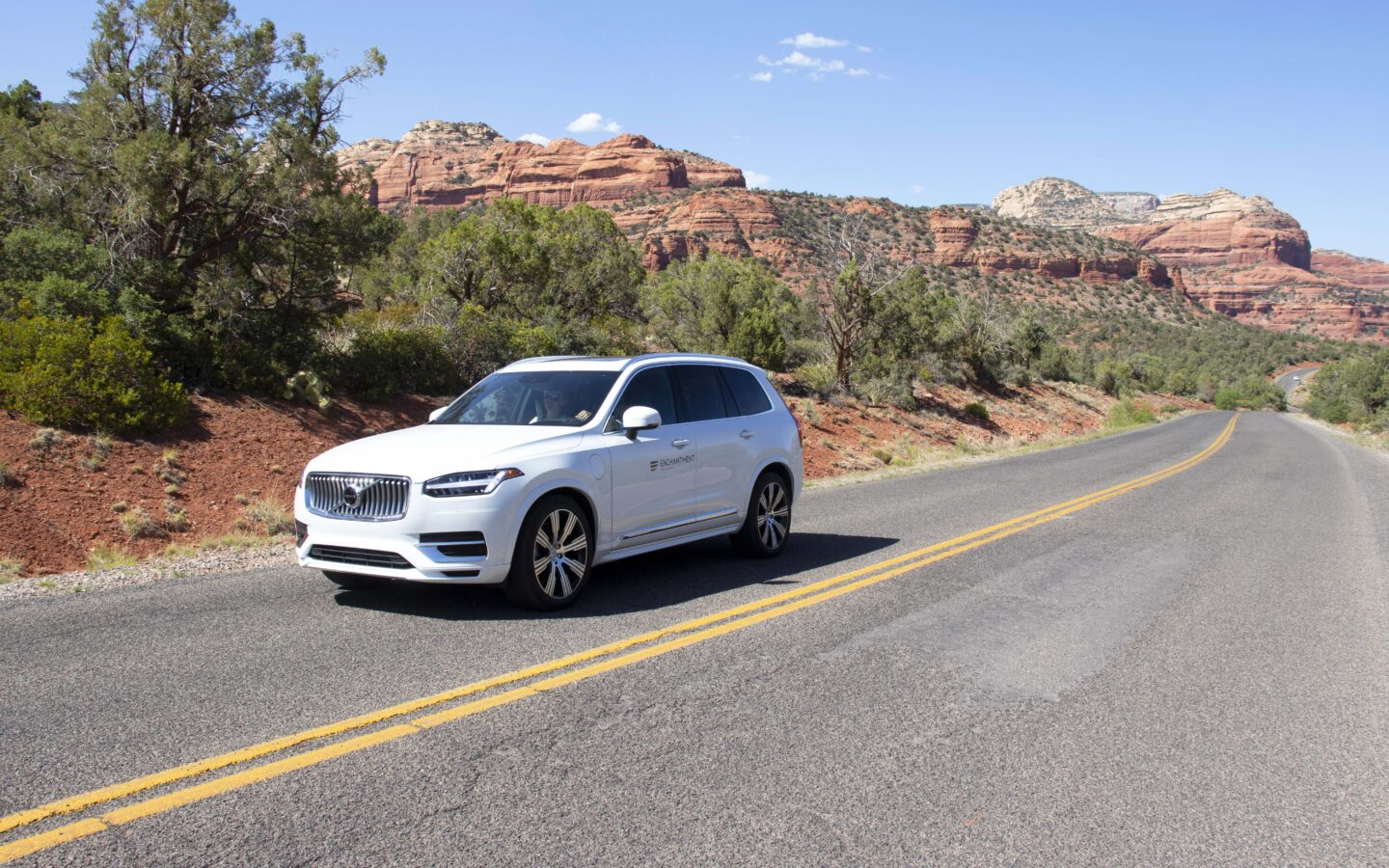 white car in the road with tress and canyon mountains in the background