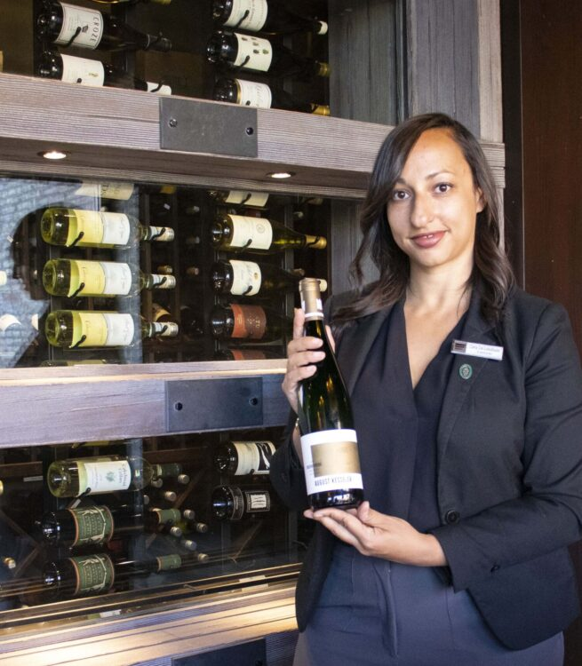 Sommelier holding a wine bottle with cabinet of wines at her back