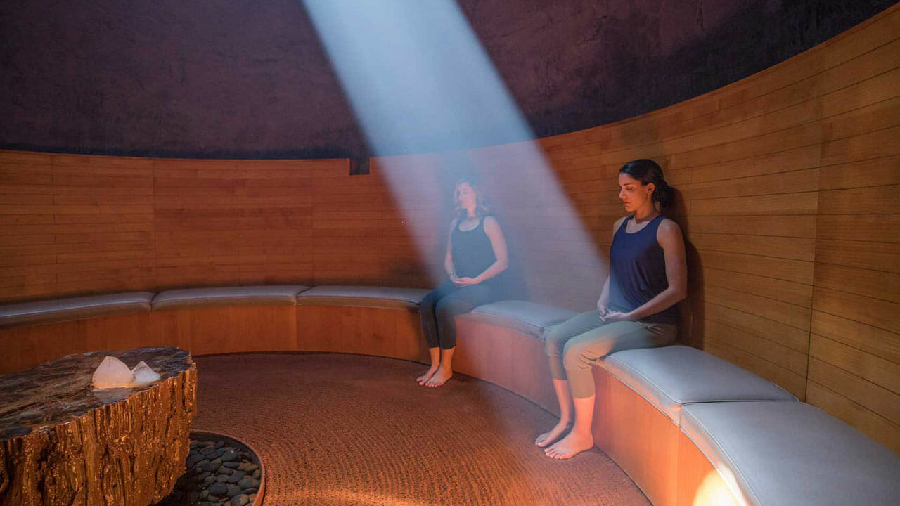 Two women meditating in grotto with sun shining in from the ceiling