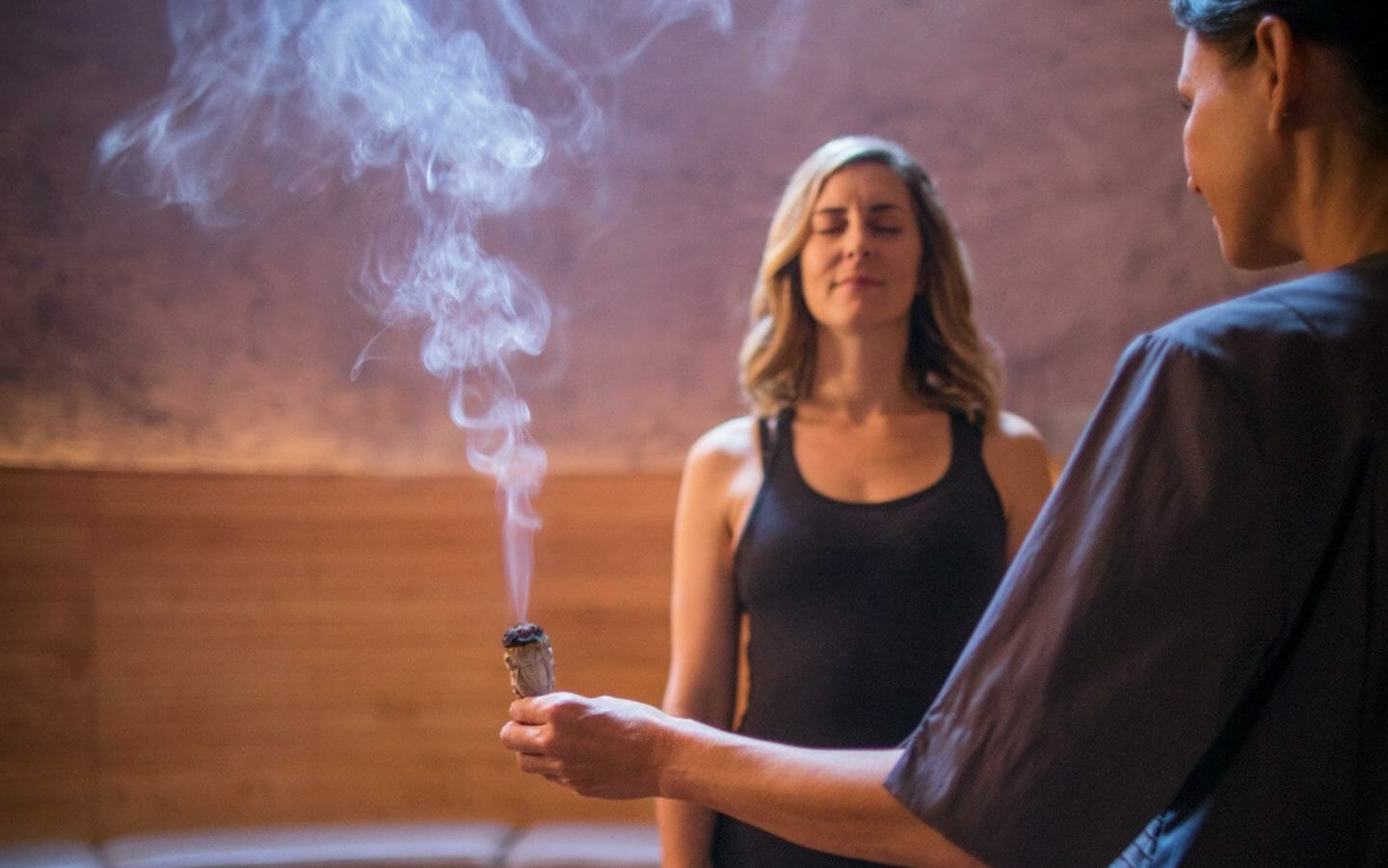 two women in a spa room with sage burning