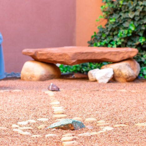 person walking on red dirt with circle of rocks