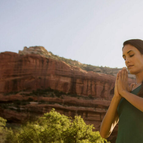 People meditating with canyon in the background