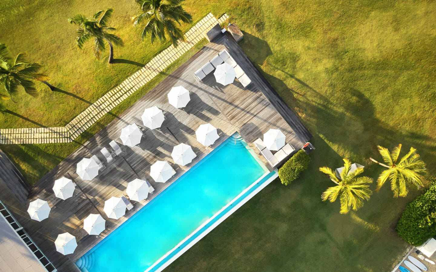 Aerial photo of pool and deck with chairs and umbrellas