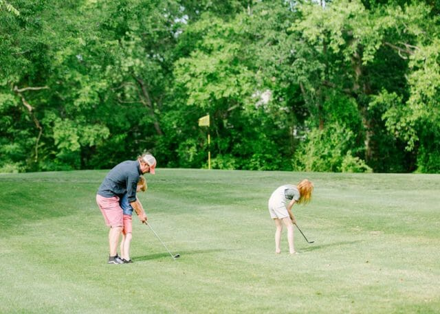 man with 2 children playing golf