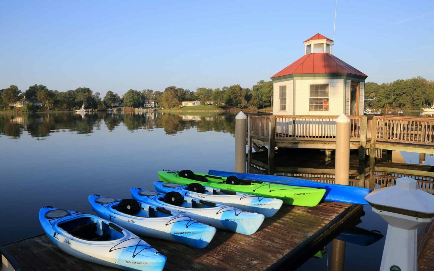 multicoloured kayaks on a dock at the water