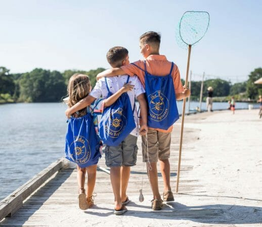 Three kids on a pier with a fishing net at our Chesapeake Bay family resort