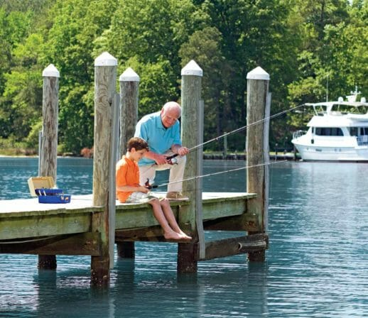 grandparent and grandchild fishing on a dock