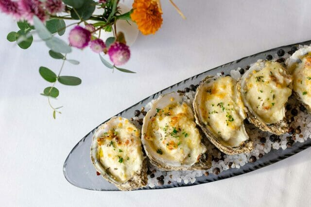 five oysters prepared on a serving tray