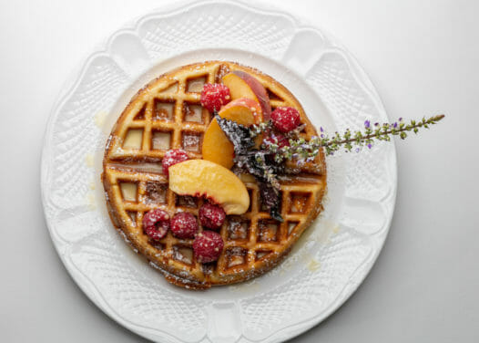 belgian waffle topped with peach slices, raspberries, and icing sugar