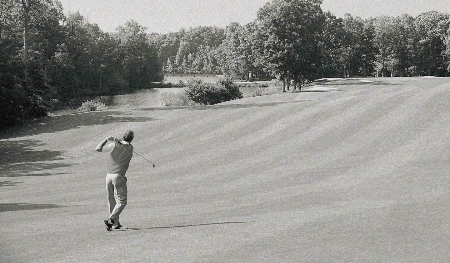 grayscale photo of man playing golf