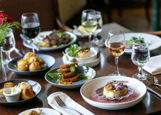assorted cooked foods and glasses of wine on a wooden table