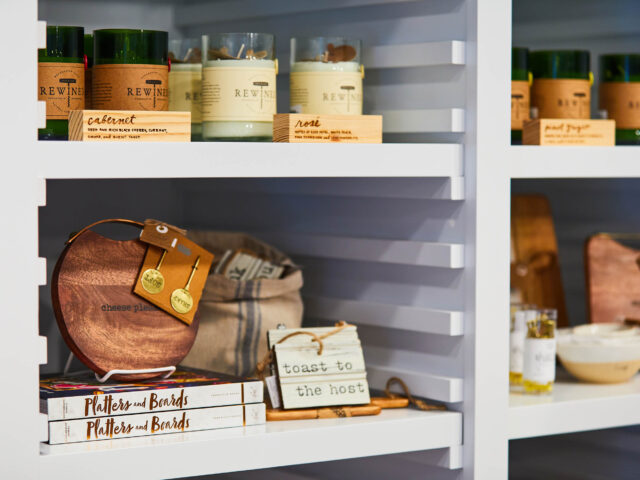 Candles, cheese board and books on a shelf
