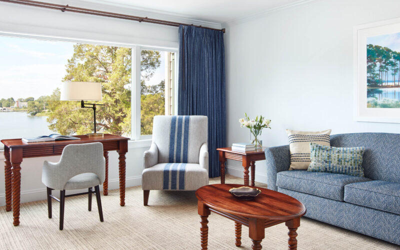 Room with large window, couch, chairs and tables