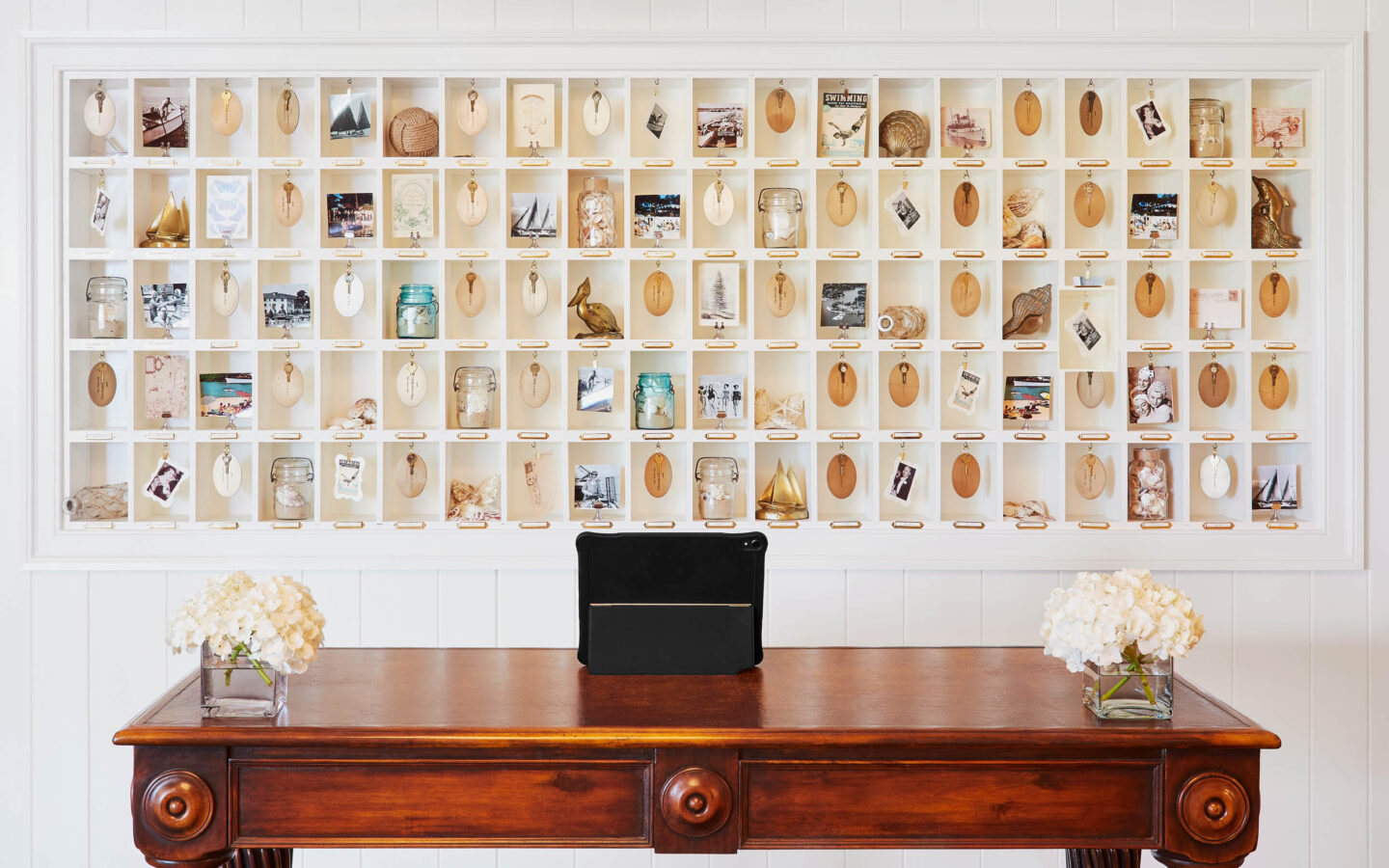 wall with small compartments of keys with decorative keychains behind a counter