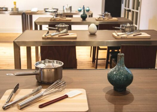 room with tables covered with pot utensils and cutting board