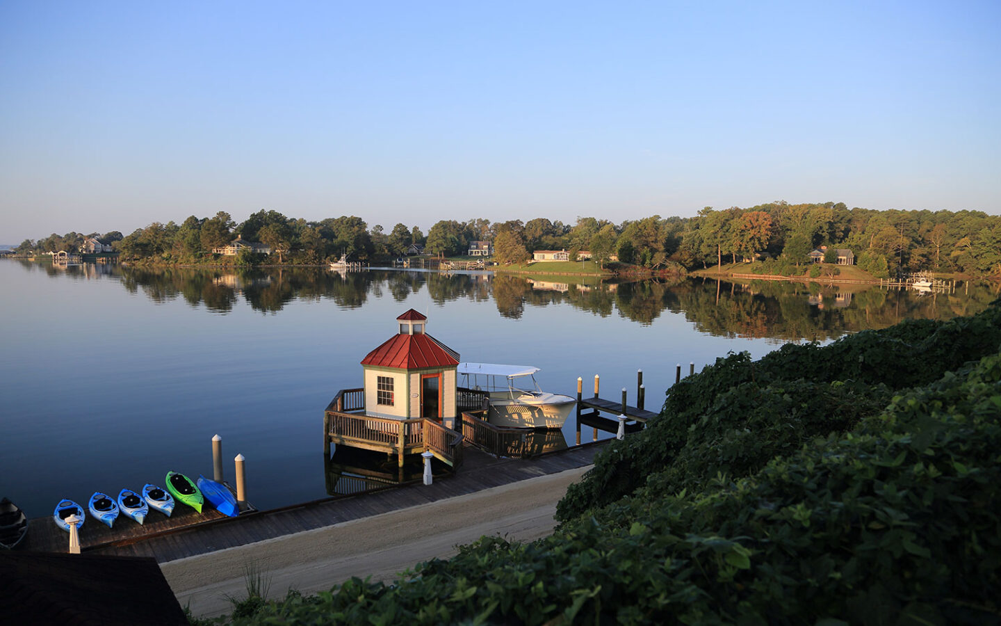lake with a dock next to a small gazebo with a red roof