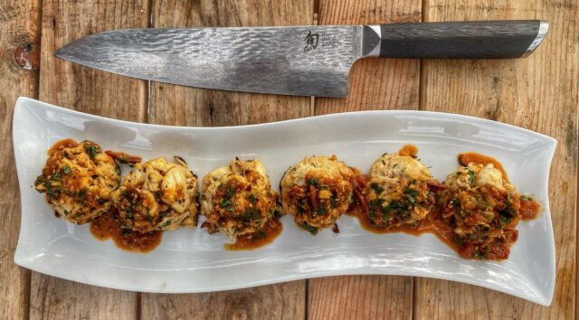 plate of crab cakes with a large knife