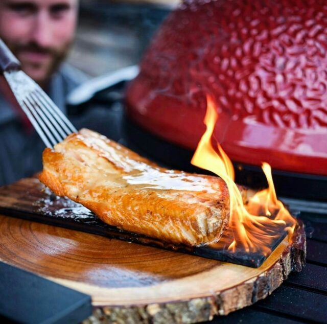 cooked fish on a flaming wood board