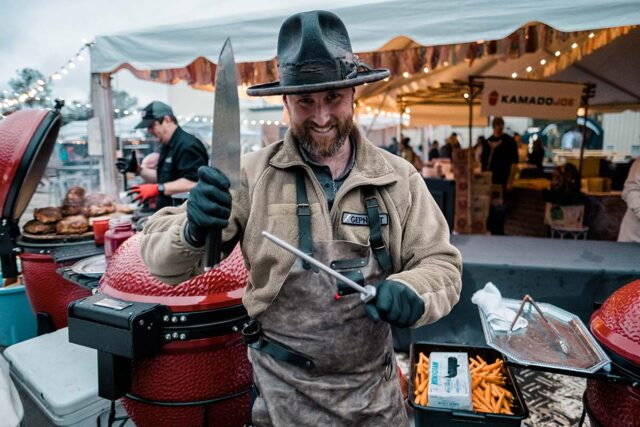 chef in tall brimmed hat and apron holding two knives close to BBQ