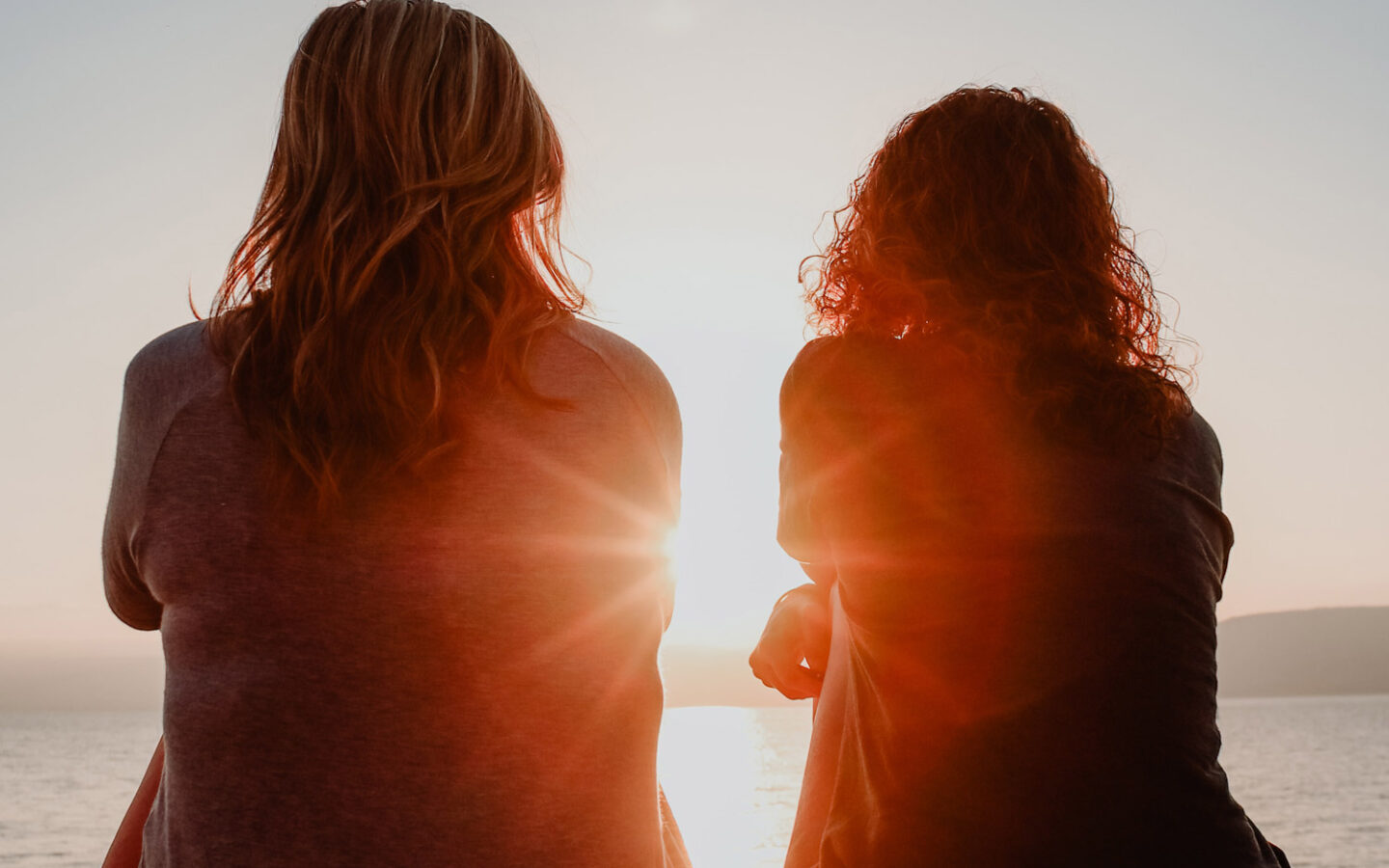 two women sit on dock over water during sunset