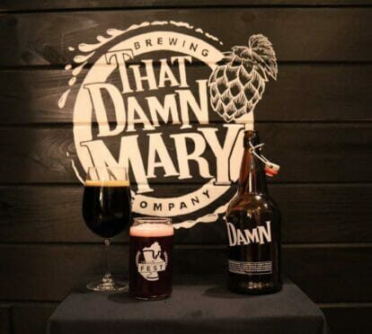 that damn mary logo on a wall with alcoholic beverages displayed in front