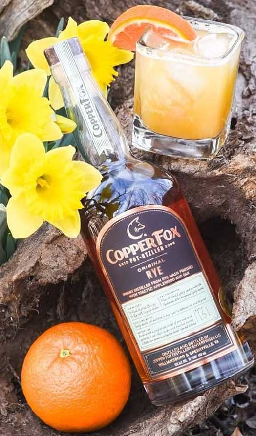 bottle of copper fox whiskey on a log surrounded by flowers and oranges