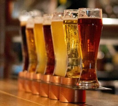 different coloured beer glasses lined up on a bar counter
