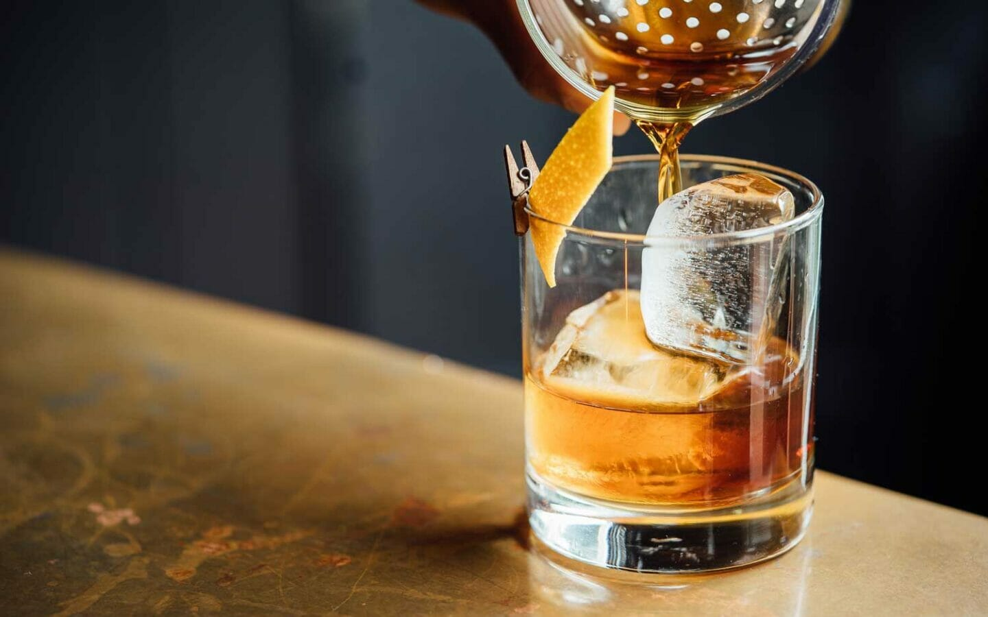 whiskey being poured into a glass with an ice cube and an orange slice inside