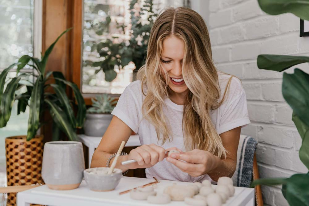 photo of Claire Jensen creating small objects out of clay